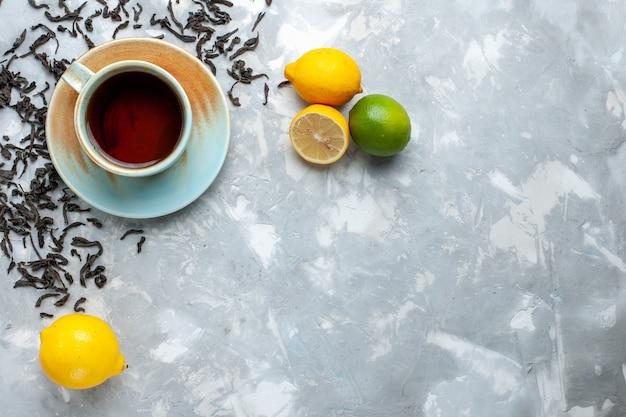 Vista dall'alto tazza di tè con chicchi di tè essiccati freschi e limone sul tavolo luminoso, colazione da bere tè