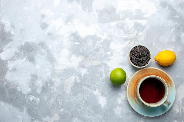 Vista dall'alto tazza di tè con limoni freschi e tè essiccato sul tavolo luminoso, bevanda color agrumi di frutta del tè