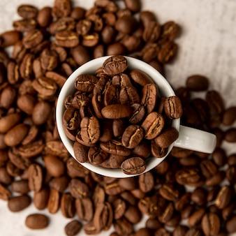 Vista dall'alto tazza piena di chicchi di caffè tostati