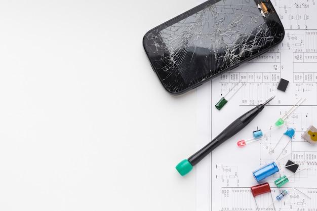 Vista dall'alto telefono rotto con componenti elettronici