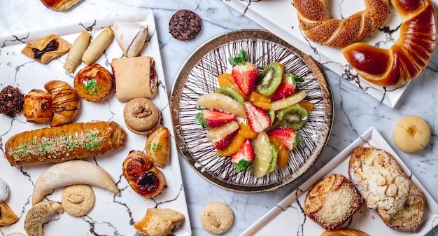 Vista dall'alto torta di frutta con crema alla vaniglia cioccolato kiwi ananas fragola arancia e pasticcini sul tavolo