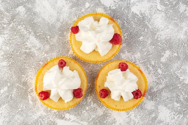 Vista dall'alto torte con crema gustosissima al forno progettate con lampone sulla scrivania grigia zucchero dolce cuocere al forno crema di biscotti