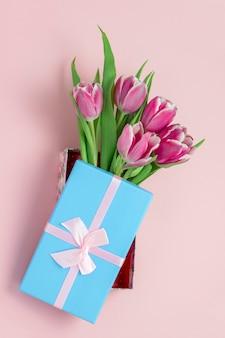 Vista dall'alto tulipani rosa in una scatola blu con fiocco in nastro di raso rosa su un rosa pastello