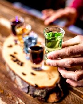 Vista dall'alto un uomo beve scatti colorati con chicchi di caffè su un pezzo di legno