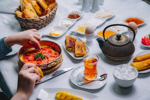 Vista dall'alto una donna fa colazione uova fritte con pomodori in padella con frittelle e un bicchiere di tè