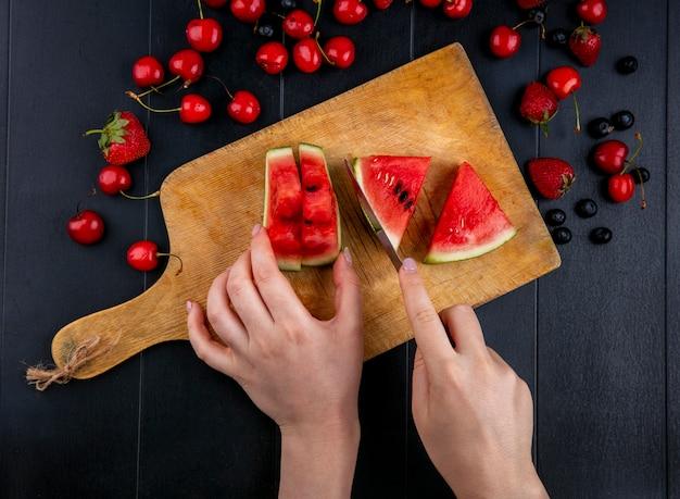 Vista dall'alto una ragazza taglia fette di anguria su una tavola con ciliegie e fragole su sfondo nero