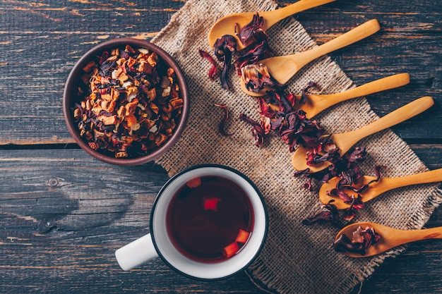 Vista dall'alto una sorta di tè in una ciotola e cucchiai con una tazza di tè sul panno di sacco e fondo in legno scuro. orizzontale