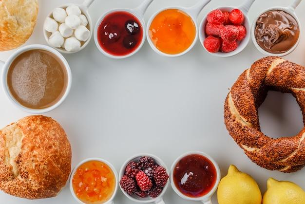 Vista dall'alto una tazza di caffè con marmellate, lamponi, zucchero, cioccolato in tazze, bagel turco, pane, limone su superficie bianca