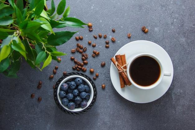 Vista dall'alto una tazza di caffè con mirtilli, cannella secca, pianta su superficie grigia. orizzontale
