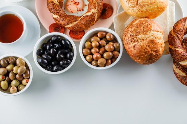 Vista dall'alto uova con salsiccia nel piatto con una tazza di tè, bagel turco, olive, pane sulla superficie bianca