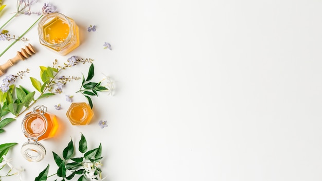 Vista dall'alto vasetti di miele con foglie