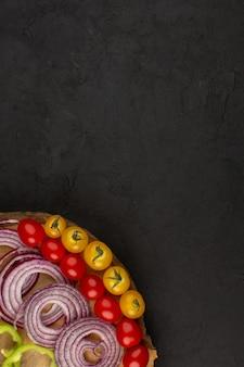 Vista dall'alto verdure come cipolle pomodori sul pavimento scuro