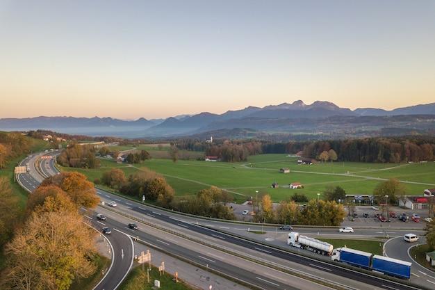 Vista dall'alto verso il basso della strada da uno stato all'altro dell'autostrada senza pedaggio con le automobili di traffico commovente nella zona rurale.