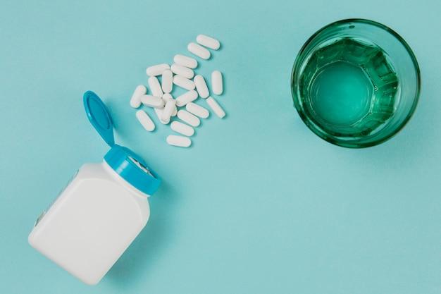 Vista dall'alto vetro con acqua e medicina sul tavolo