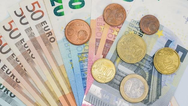 Vista dall'alto vicino pila di banconote e monete euro
