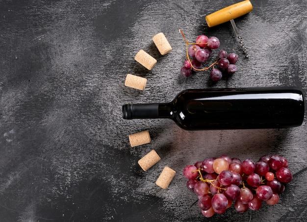 Vista dall'alto vino rosso con uva e copia spazio a sinistra su pietra nera orizzontale