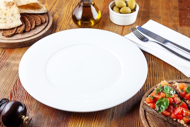 Vista dall'alto vuoto piatto bianco per pasto. piatto bianco per servire il cibo in composizione con, pomodori secchi, bruschetta e utensili su fondo di legno. disteso