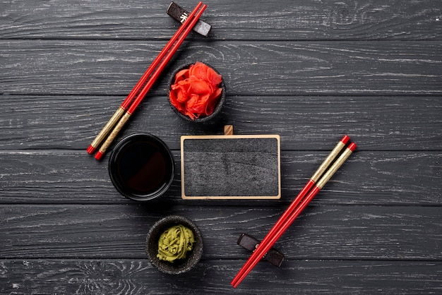 Vista dall'alto wasabi allo zenzero e ciotole di salsa di soia con taccuino in bianco