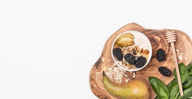 Vista dall'alto yogurt con avena, frutta e miele con copia-spazio