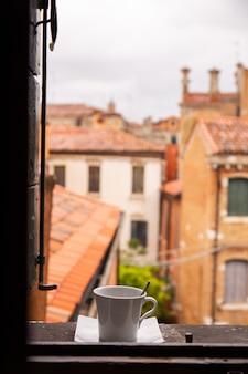 Vista dalla finestra sulla città con la tazza di caffè del davanzale a venezia, italia.