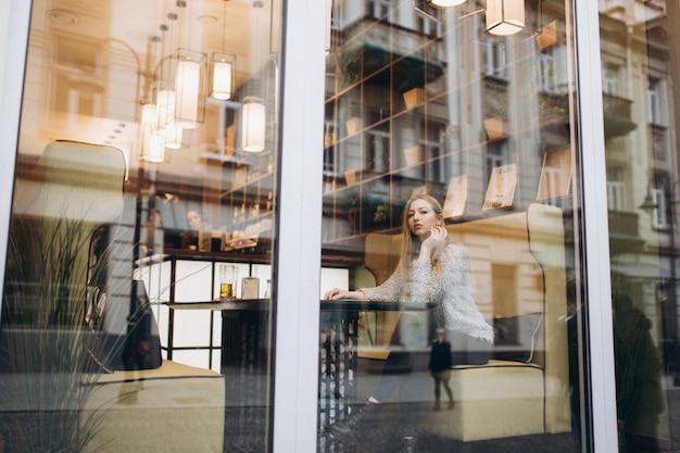 Vista dalla strada. giovane bella donna bionda seduta in un bar nel centro della città