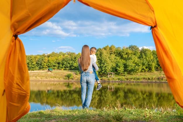 Vista dalla tenda da campeggio. la donna gode della natura tenendo il bambino in mano. escursioni con bambino