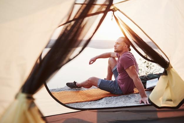 Vista dalla tenda del viaggiatore con lo zaino che si siede in cima alla montagna che gode della vista costeggia un fiume o un lago. in viaggio lungo le montagne e la costa, la libertà e il concetto di stile di vita attivo