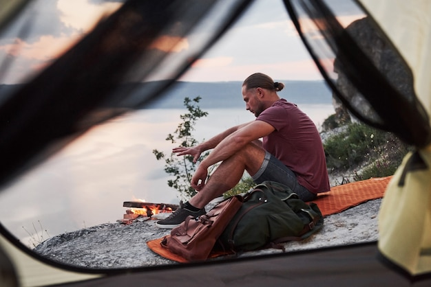 Vista dalla tenda del viaggiatore con lo zaino che si siede in cima alla montagna che gode della vista costeggia un fiume o un lago. libertà e concetto di stile di vita attivo