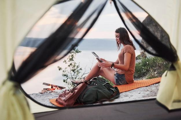 Vista dalla tenda della donna con lo zaino che si siede in cima alla montagna che gode della vista costeggia un fiume o un lago. libertà e concetto di stile di vita attivo