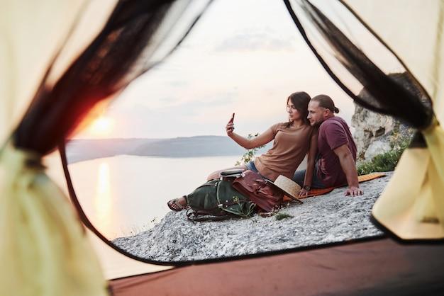 Vista dalla tenda delle coppie che si trovano una vista del lago durante l'escursione. avel lifestyle concept vacanze avventura all'aperto