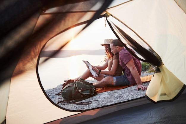 Vista dalla tenda delle coppie con la mappa che si trova una vista del lago durante l'escursione. avel lifestyle concept vacanze avventura all'aperto