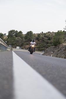 Vista dalla terra del giovane in sella a una moto su strada in montagna.