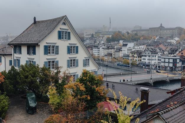 Vista del centro urbano di zurigo attraverso il panorama del fiume di limmat sulla costruzione, tempo nuvoloso