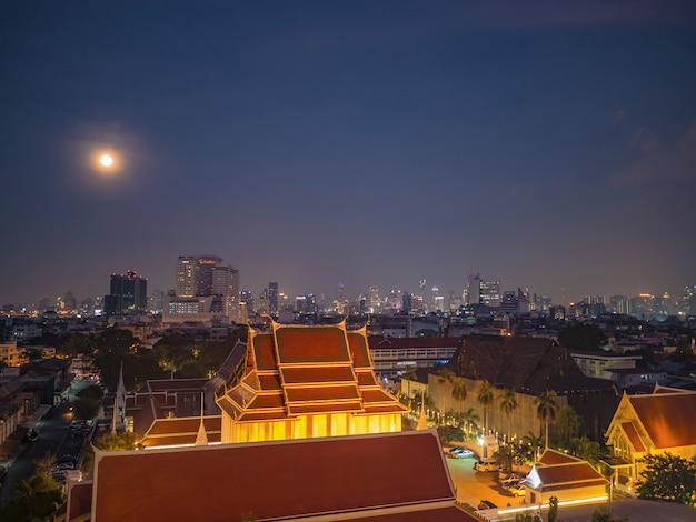 Vista del cielo di bangkok cityscape e della luna piena dal supporto dorato al tempio tailandia del saket del wat