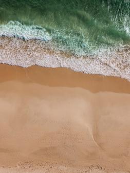Vista del flusso del mare sulla spiaggia sabbiosa