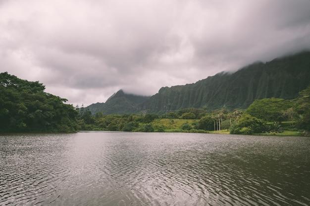 Vista del lago e delle montagne nel giardino botanico di hoomaluhia, isola di oahu, hawai
