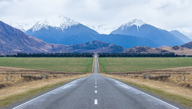 Vista del lungo rettilineo strada ghiacciata che porta verso le montagne isola del sud della nuova zelanda