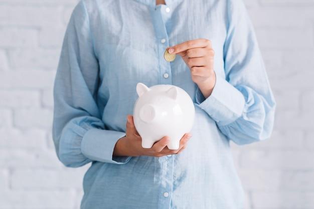 Vista del midsection della mano di una donna che inserisce moneta nel porcellino salvadanaio bianco
