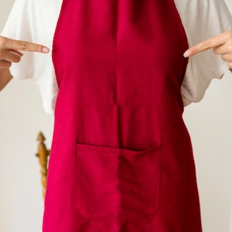Vista del midsection di una donna che indica dito al grembiule rosso