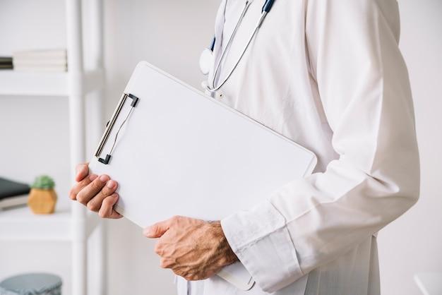Vista del midsection di una lavagna per appunti della tenuta della mano di medico con libro bianco in bianco