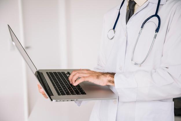 Vista del midsection di una mano di medico facendo uso del computer portatile