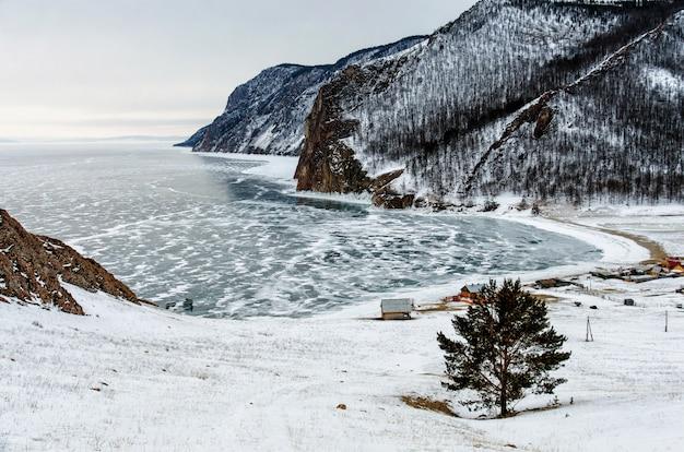 Vista del paesaggio invernale in siberia con il lago baikal congelato in lontananza. inverno in russia