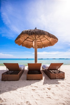 Vista del paradiso di piacevole plage sabbiosa vuota tropicale con ombrellone e sedia a sdraio