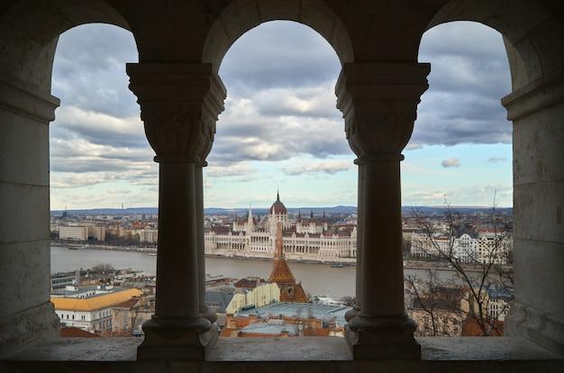 Vista del parlamento di budapest da dietro alcune colonne sul fiume.