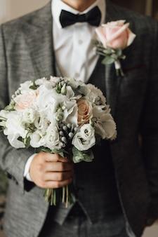 Vista del petto di un uomo vestito in elegante abito grigio con bouquet da sposa e boutonniere