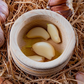 Vista del primo piano degli spicchi d'aglio sbucciati in frantoio di aglio sul fondo della paglia