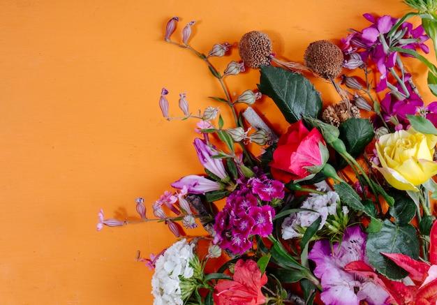 Vista del primo piano dei fiori dalla destra e dall'arancia con lo spazio della copia