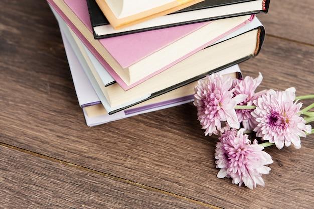 Vista del primo piano dei libri e del fiore sulla tavola di legno