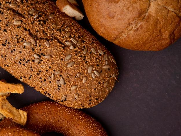 Vista del primo piano dei pani come pannocchia e baguette del bagel su fondo marrone rossiccio con lo spazio della copia