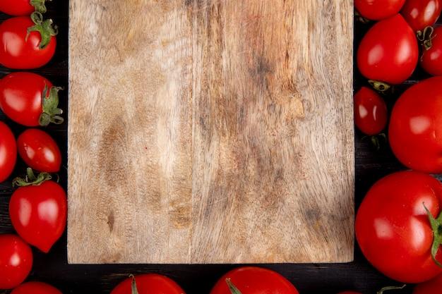 Vista del primo piano dei pomodori intorno al tagliere sulla tavola di legno